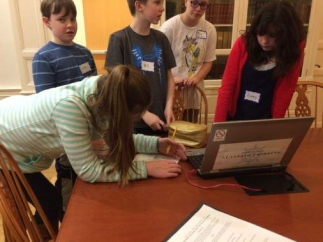 Teens working on a word puzzle and a song clue from the laptop