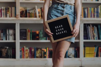 """Girl holding sign that says """"read good books"""""""