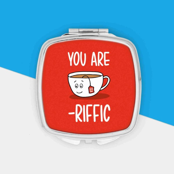 """Silver pocket mirror with cup of tea illustration and the phrase """"You Are Tea-Riffic"""" on the top."""