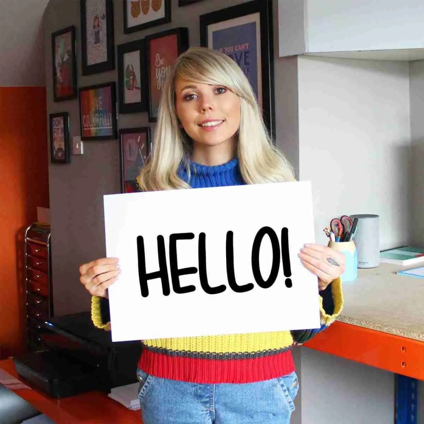 Toni Pilling holding up hello sign in office
