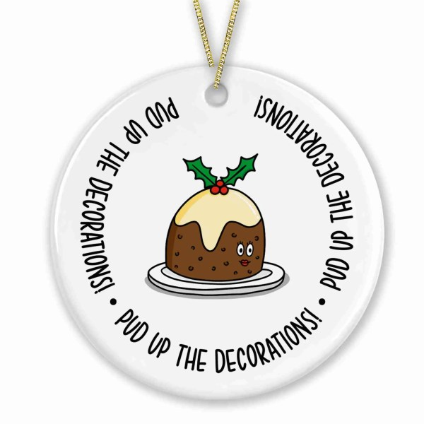"""Circle shaped bauble with Christmas pudding illustration and the phrase """"Pud up the decorations!"""" on the front."""