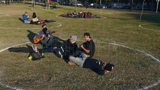 La gente disfruta al aire libre, en zonas demarcadas para mantener la distancia social.