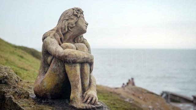 Escultura de la mujer sentada que se toma las piernas mientras mira hacia el mar.