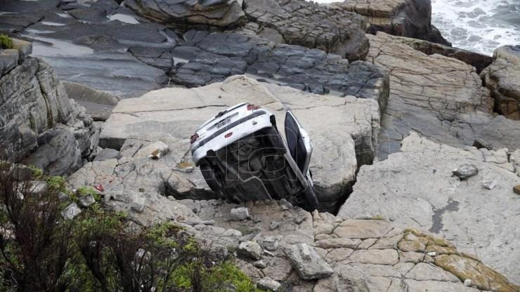 La conductora de un Peugeot 207 perdió el control de su rodado en una curva, tras lo cual se subió a la vereda, rompió el paredón y cayó al vacío unos 6 metros, por lo que se incrustó entre las rocas. Fot