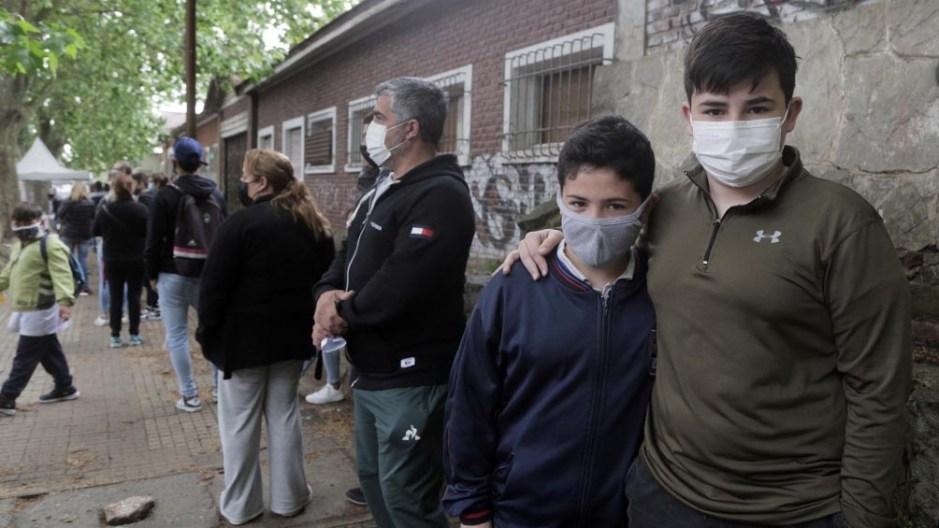 Agustín (10) y Nicolás (15) esperan en el Hipódromo de La Plata ingresar al predio para su vacunación. (Foto Leo Vaca)