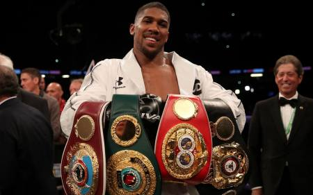 Anthony Joshua celebrates with his belts after victory over Joseph Parker