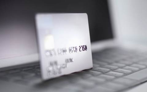 Close-up of silver payment card standing on computer keyboard