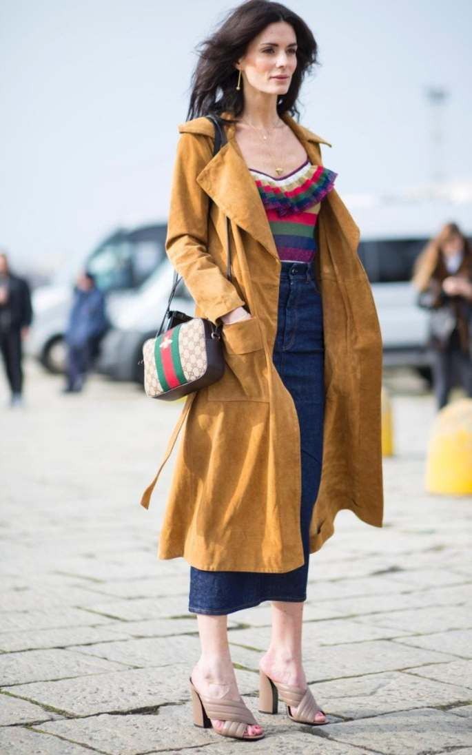 Hedvig Opshaugtones down her maximal ruffled Gucci striped top with a denim midi and dark tan trench
