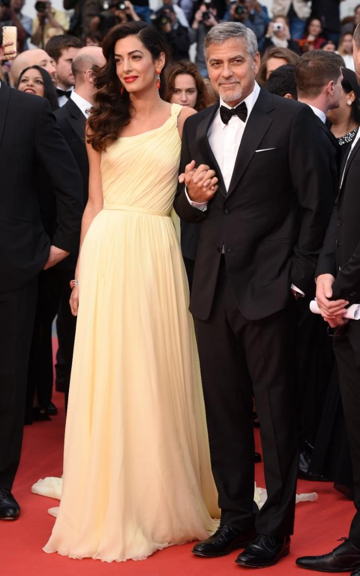 Amal Clooney joins her husband George Clooney, who stars in Money Monster, on the red carpet in a lemon flowing gown