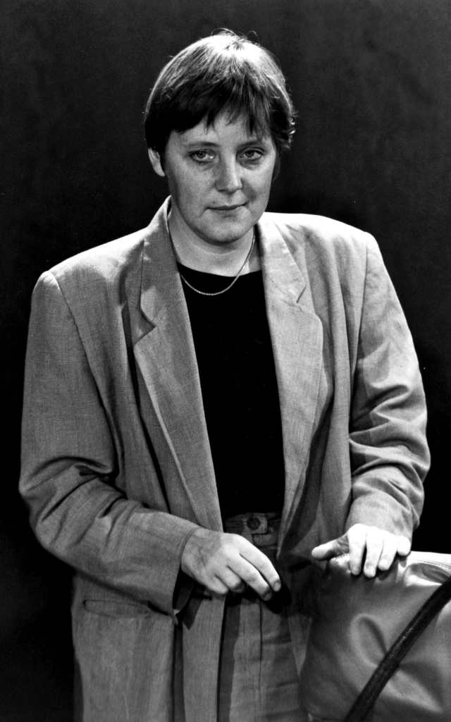 An archive shot in black & white of a younger Angela Merkel in a grey  oversiszed trousersuit & black sweater. | As Germany goes to the polls, how  Angela Merkel dresses for