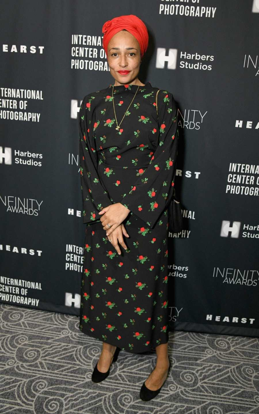 Zadie Smith at The International Center Of Photography's 35th Annual Infinity Awards wearing a red turban and floral dress