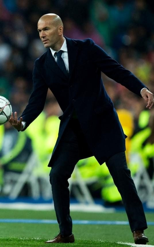 Zinedine Zidane during Real Madrid's match against Wolfsburg, standing on the touchline, chucking the ball back to a player