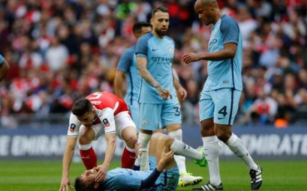 Manchester City's David Silva holds his leg after a challenge from Arsenal's Gabriel Paulista