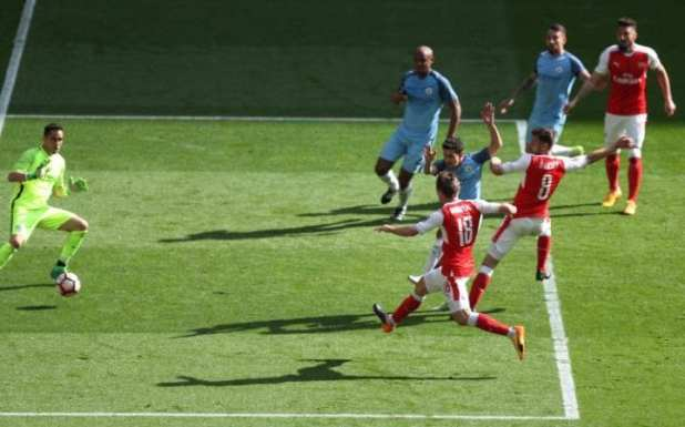 Nacho Monreal (bottom) of Arsenal scores his side's first goal