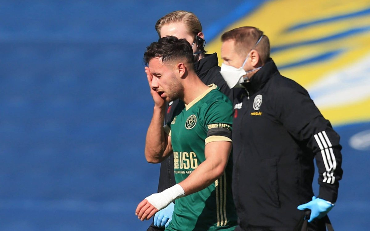 Sheffield United's English defender George Baldock goes off after taking a knock in a challenge during the English Premier League football match between Leeds United and Sheffield United at Elland Road in Leeds, northern England on April 3, 2021.