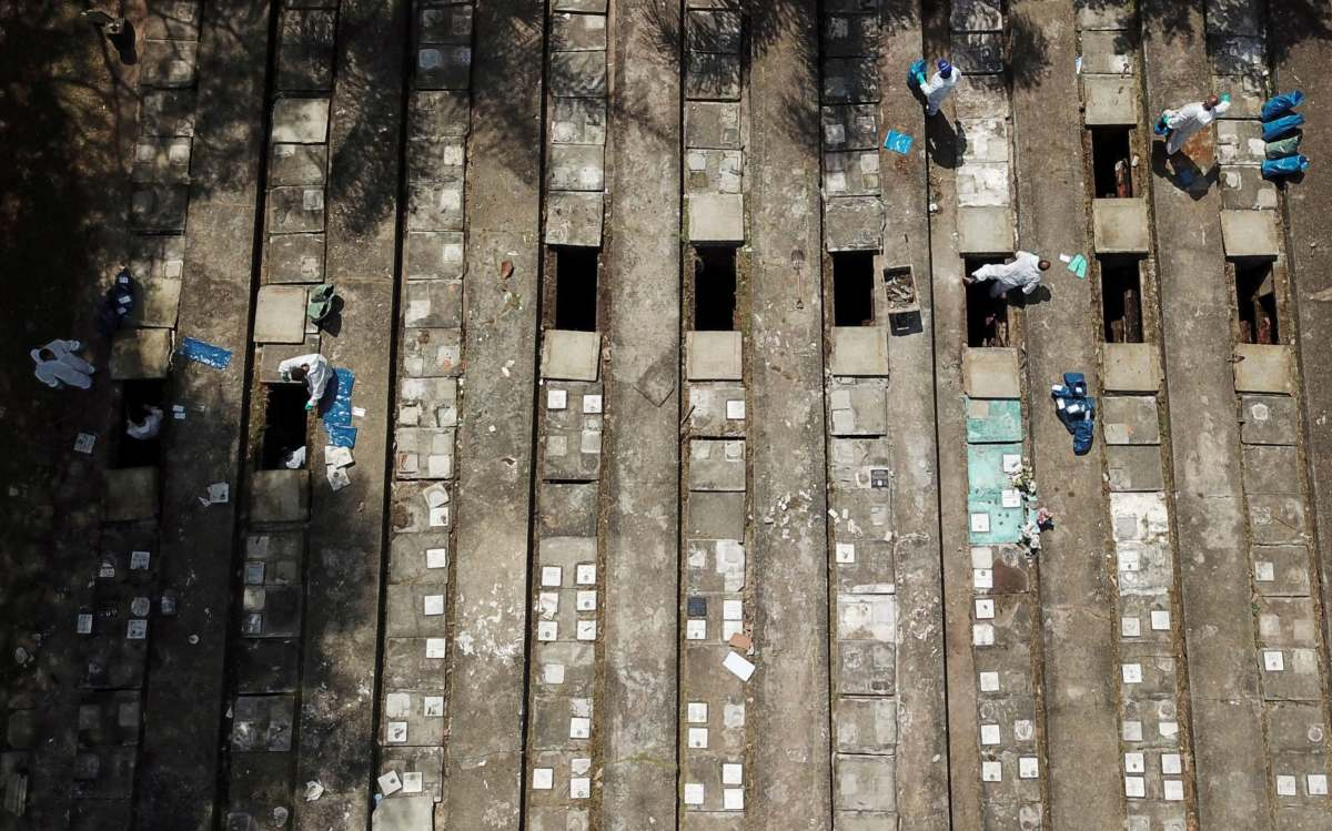 Gravediggers perform exhumations to open space on cement graves in Sao Paulo