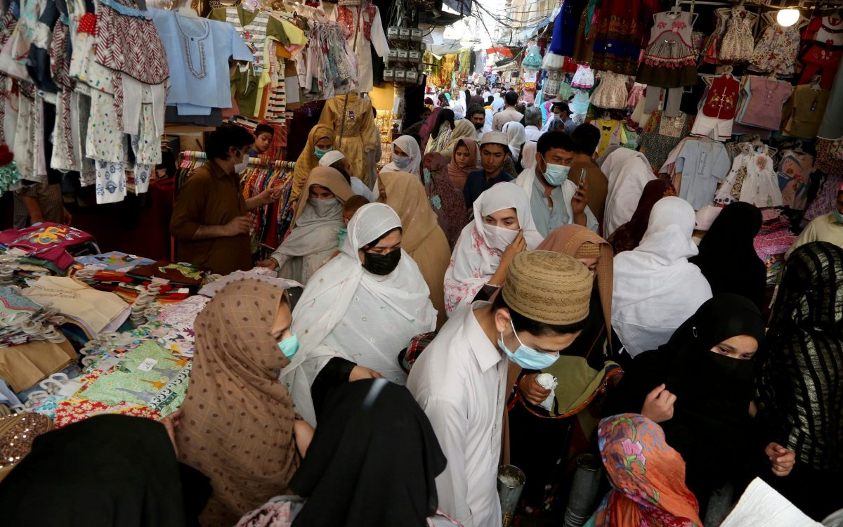 People ignore social distancing while shopping at a market after the government announced new restrictions to help control the spread of the coronavirus, in Peshawar, Pakistan