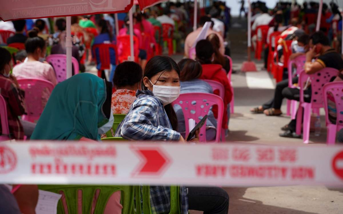 People wait to get tested inside a red zone in Phnom Penh