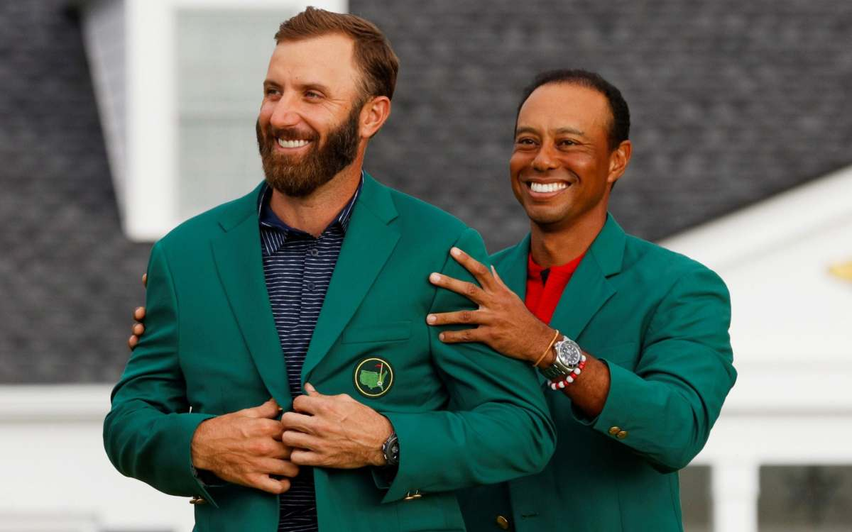 Dustin Johnson of the U.S. is presented with the green jacket by Tiger Woods