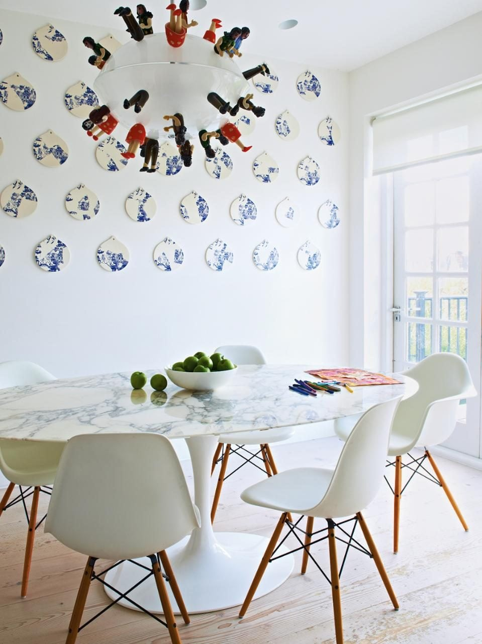 The kitchen wall displays a Livia Marin mural, and a glass pendant light features replica Brazilian dolls for a fun touch