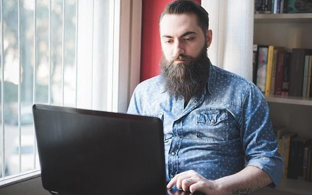 A young bearded man using laptop on floor