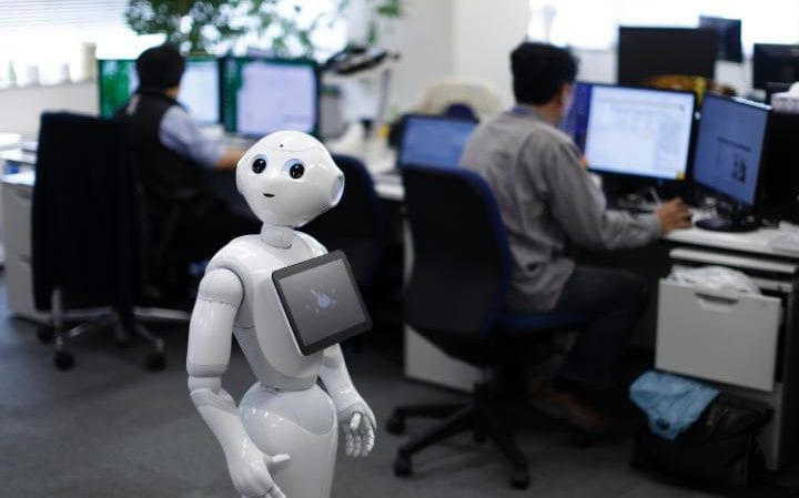 Pepper the humanoid robot standing as employees work in the Orange Arch Inc offices in Tokyo