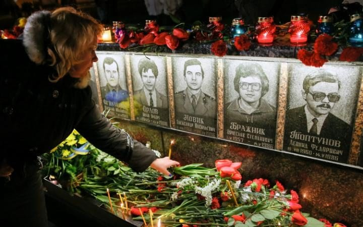 Ukrainians light candles and lay flowers at the memorial for 'liquidators' who died during cleaning up works after the Chernobyl nuclear power plant disaster, during a ceremony in Slavutich city, some 190 km north of the capital Kiev, Ukraine, early 26 April 2016.