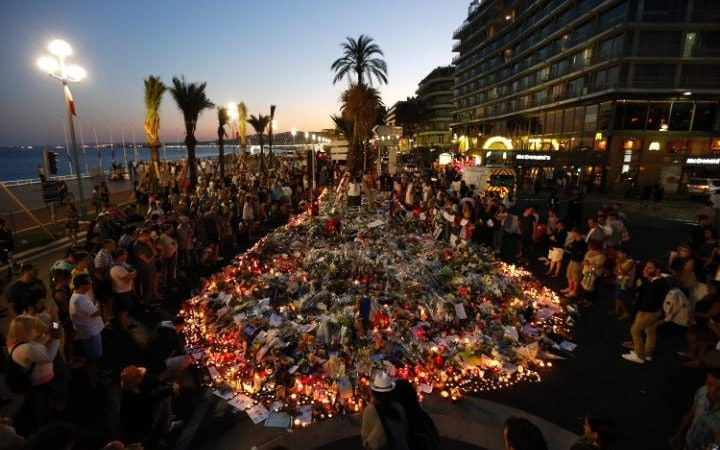 People gather at a makeshift memorial on the Promenade des Anglais in Nice