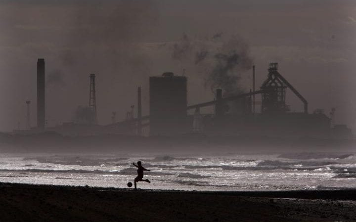 A local plays football at high tide on Redcar beach in the shadow of the Corus Steelworks in Teeside, on July 21, 2008, in Middlesborough, England