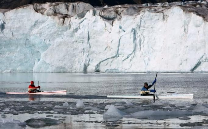 British explorer Lewis Gordon Pugh (right) kayaks past polar ice in the Arctic