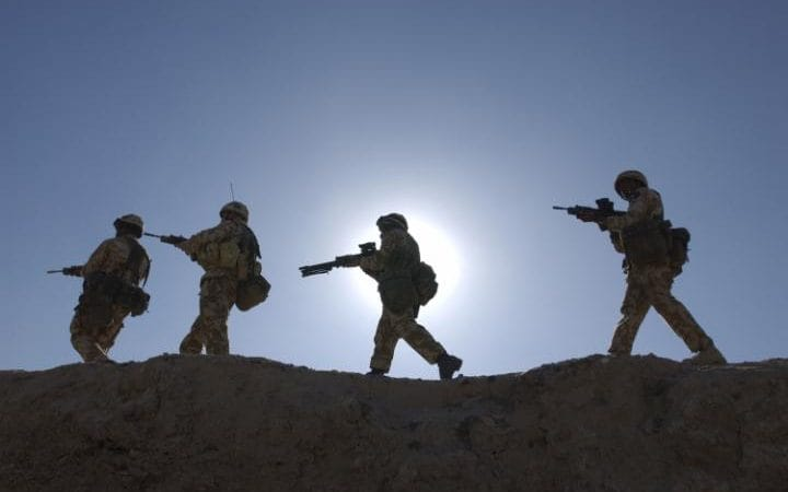 British soldiers in 1 Battalion the Royal Irish Regiment, 16 Air Assault Brigade, silhouetted against the sun as they move along a ridge during a patrol in the early days of the war against Iraq, March 2003