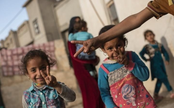 Children make victory signs outside their homes in the village of Khaladia