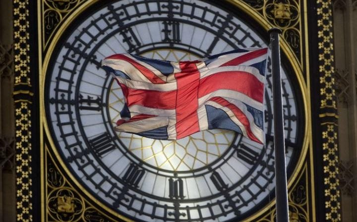 The Union flag is seen flapping in the wind in front of one of the faces of the Great Clock atop the landmark Elizabeth Tower that houses Big Ben