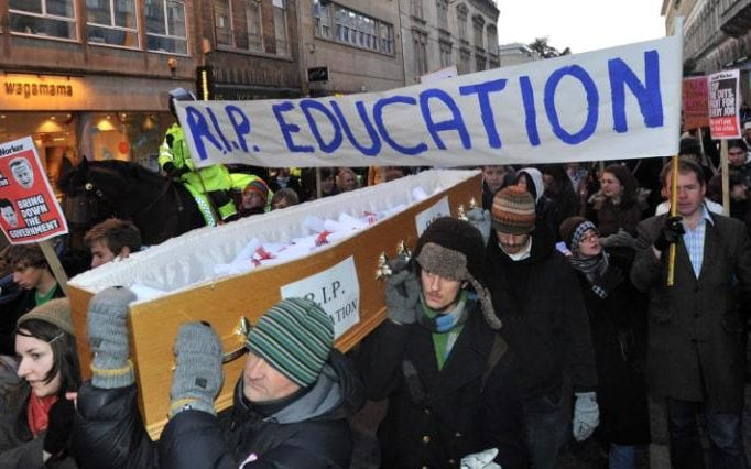The students carry a coffin and a banner reading RIP Education