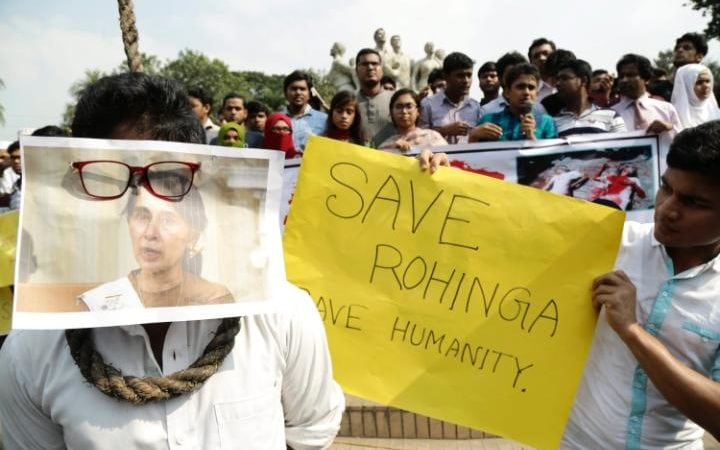 A Bangladeshi student covers his face with a photo of Myanmar's State Counsellor and Foreign Minister Aung San Suu Kyi and carry banners reading 'Save Rohingya save humanity'