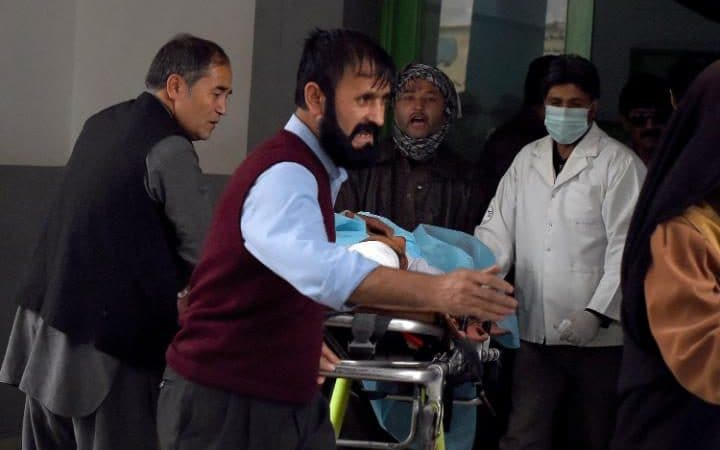 Afghan relatives and doctors move a wounded Afghan man at the Estiqlal Hospital after a massive suicide blast at a Shia mosque