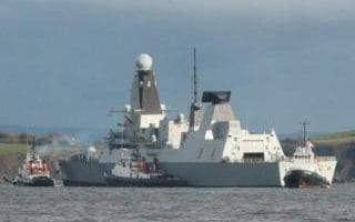The Type 45 destroyer HMS Duncan being assisted by dockyard tugs