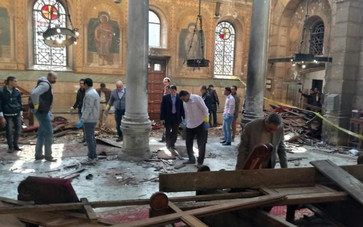 Egyptian security forces examine the scene inside St. Mark Cathedral in central Cairo, following a bombing, Sunday, Dec. 11,