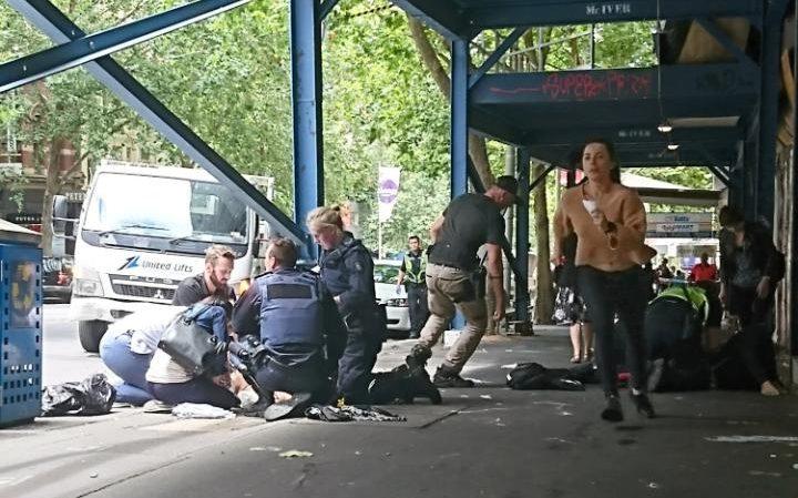 Los miembros del reloj público como la policía y los servicios de emergencia para asistir a una persona lesionada después de un auto chocó contra peatones en el centro de Melbourne