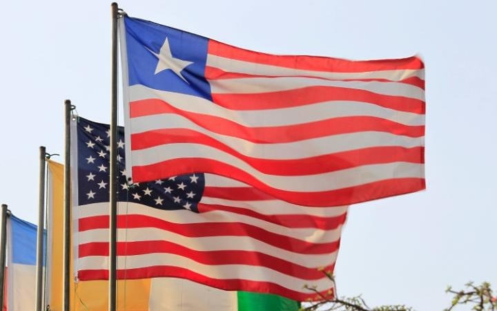 Liberian and United States national flags with similarities being flown on a roadside in downtown Monrovia, Liberia