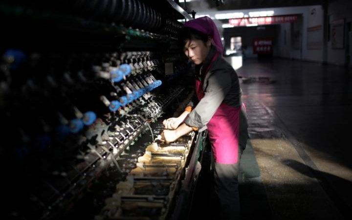 A North Korean Woman working in a dimly lit and very old-fashioned silk factory. She is wearing a pink overall with a scarf over her head.  A beam of sunlight just catches her face and forearms