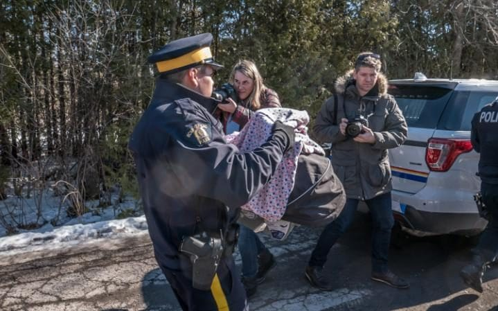 Canadian police officer carries a refugee baby