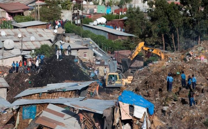 Excavators move earth as rescuers work at the site of a landslide at the main landfill of Addis Ababa