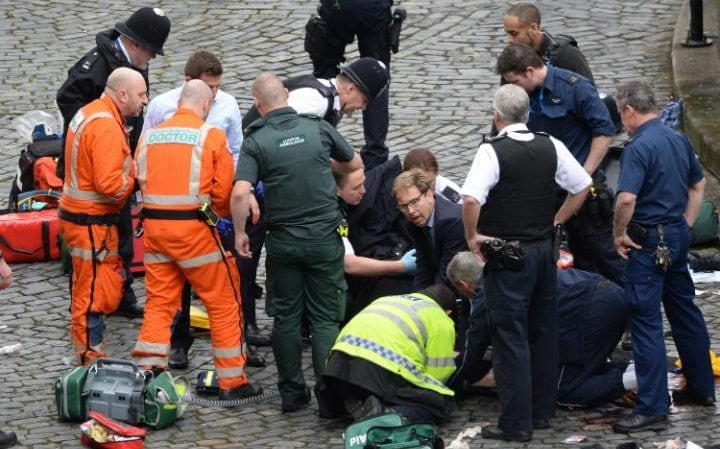Conservative MP Tobias Ellwood (centre) helps emergency services attend to the injured police officer.
