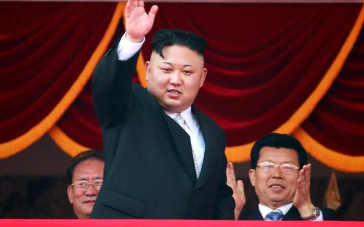 Kim Jong-un waves from a balcony during a parade for the 'Day of the Sun'