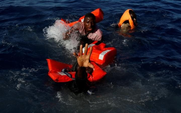 Migrants try to stay afloat after falling off their rubber dinghy during a rescue operation by the Malta-based NGO Migrant Offshore Aid Station (MOAS) ship in the central Mediterranean