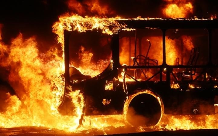 A bus burns after being set on fire by protestors in Rio during a nationwide general strike