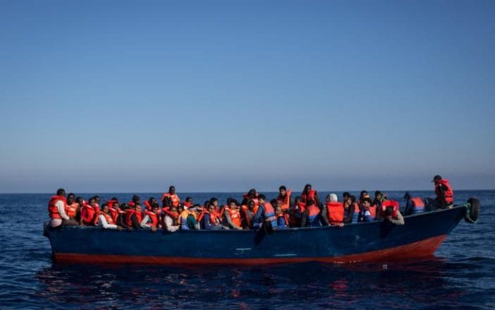 Refugees and migrants wait to be rescued from an overcrowded boat by crew members from the Migrant Offshore Aid Station (MOAS) Phoenix vessel on May 18, 2017 off Lampedusa, Italy.