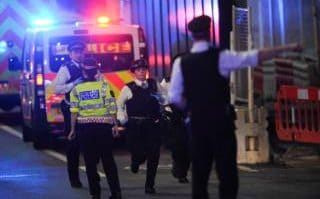 Police officers run at the scene of the terror attack on London Bridge