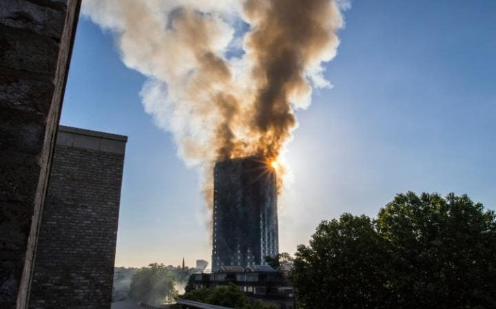 Smoke billows from the top of the Grenfell Tower block in West London this morning